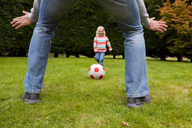 Child playing football with parent