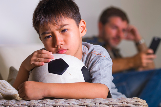 Sad child holding a football